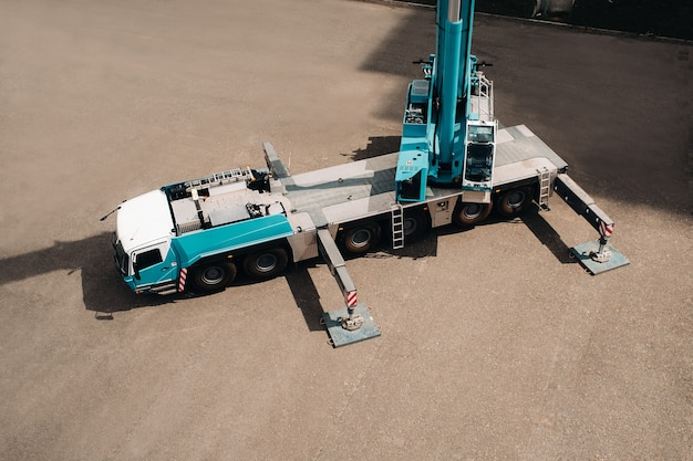 Vista da altura do guindaste pesado do carro que está aberto no estacionamento e pronto para funcionar. o guindaste de caminhão mais alto é implantado no local. a altura da lança é de 80 metros.