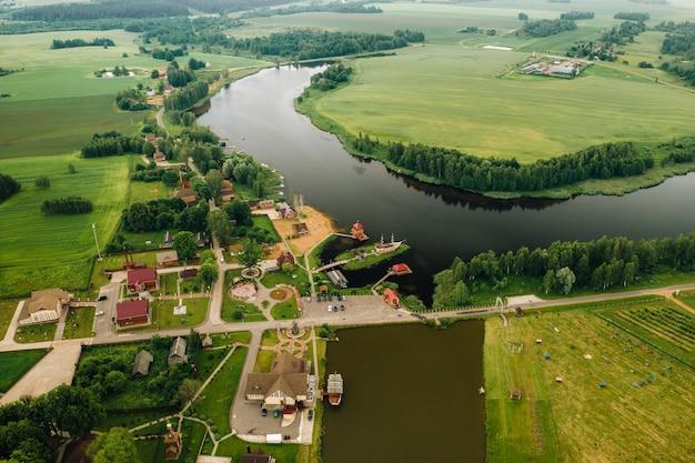 Vista da altura do lago em um campo verde na forma de uma ferradura e uma aldeia na região de mogilev.