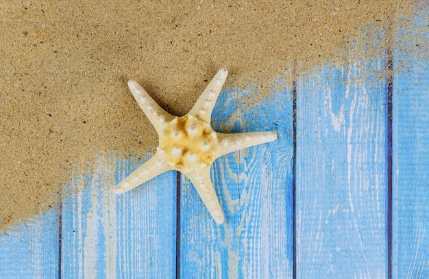 Vista da areia da praia com estrela do mar de férias de verão, areia na placa de madeira
