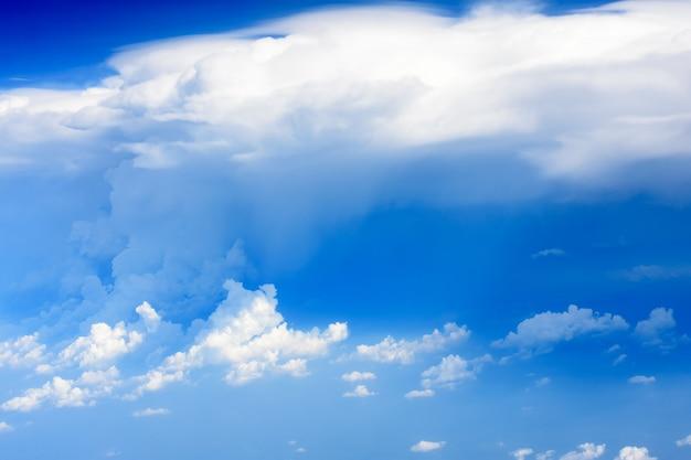 Vista da asa do avião com céu azul e nuvem branca em alto nível.