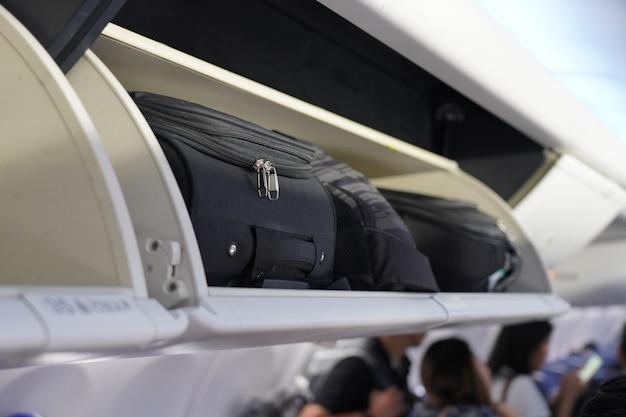 Vista da bagagem de mão na prateleira aérea na cabine do avião