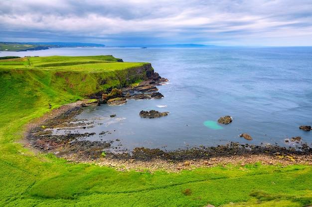 Vista da baía de portnaboe ao longo da calçada do gigante, condado de antrim, irlanda do norte, reino unido