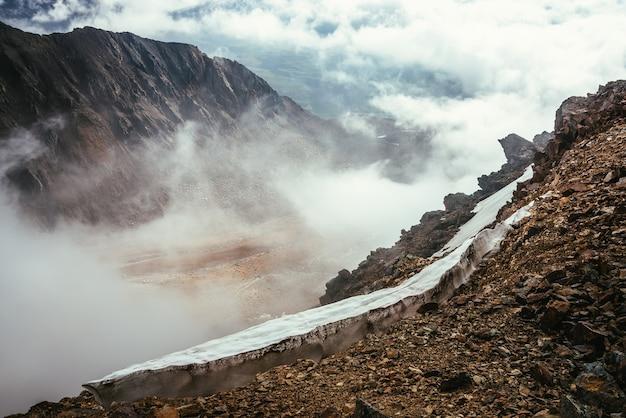 Vista da borda do precipício com pedras afiadas e cornija de neve para o vale da montanha em nuvens baixas. maravilhosas paisagens montanhosas com nuvens baixas no vale das terras altas. paisagem alpina com montanhas rochosas