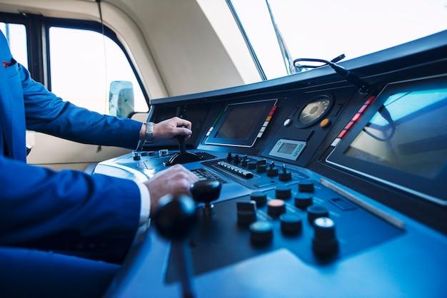Vista da cabine do trem do metrô de alta velocidade e um maquinista irreconhecível empurrando a alavanca e acelerando o trem.