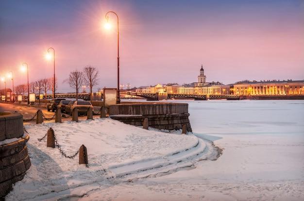 Vista da cidade à noite de inverno para a ponte do palácio e a kunstkamera em são petersburgo