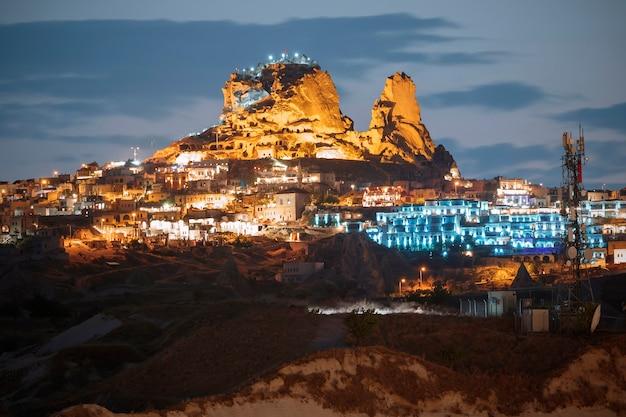 Vista da cidade antiga e do castelo uchisar à noite, capadócia, turquia