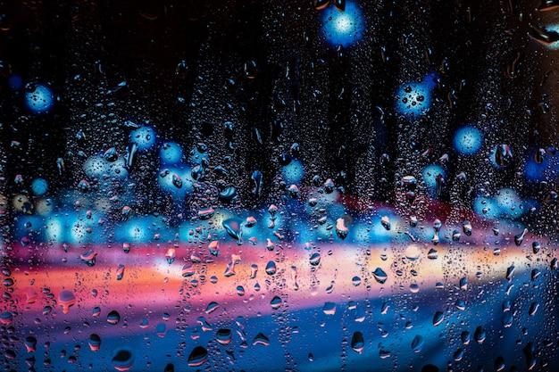 Vista da cidade através de uma janela em uma noite chuvosa com luz de estrada bokeh.