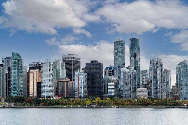 Vista da cidade de edifícios comerciais lotados e céu azul na costa no centro de stanley park, vancouver, canadá