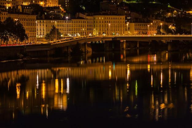 Vista da cidade de lyon, frança, com reflexos na água à noite