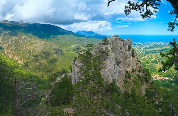 Vista da cidade de yalta da encosta do monte aj-petri (trilha botânica, crimeia, ucrânia) e cruz cristã na rocha acima.