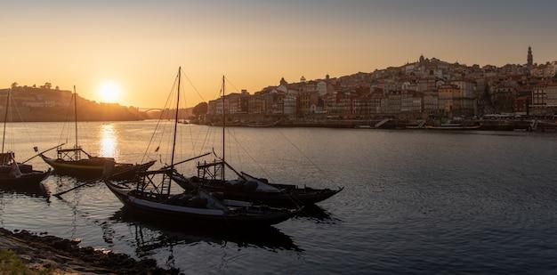 Vista da cidade do porto no pôr do sol com o rio na frente e navio transportador de vinho em primeiro plano e cidade do porto no fundo, portugal