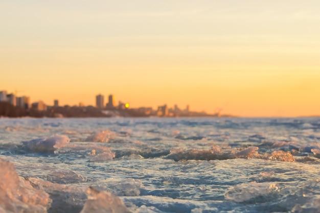 Vista da cidade no início da primavera no pôr do sol com bloco de gelo em primeiro plano e a cidade