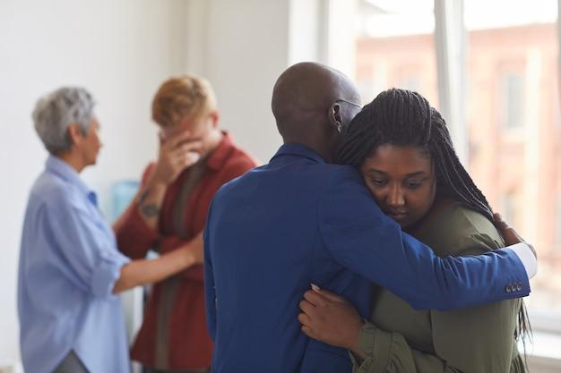 Vista da cintura para cima em dois afro-americanos se abraçando durante uma reunião do grupo de apoio, ajudando-se mutuamente com o estresse, ansiedade e tristeza, copie o espaço