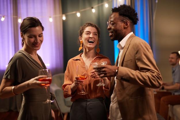 Vista da cintura para cima em um grupo multiétnico de amigos curtindo a festa dentro de casa e rindo alegremente