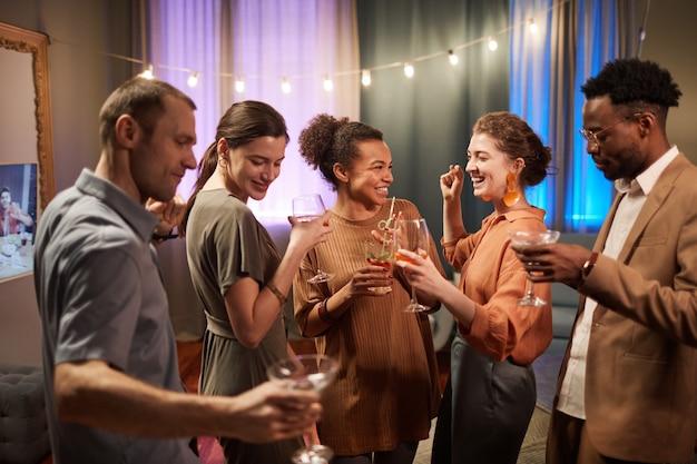 Vista da cintura para cima em um grupo multiétnico de amigos curtindo uma festa dentro de casa e bebendo coquetéis