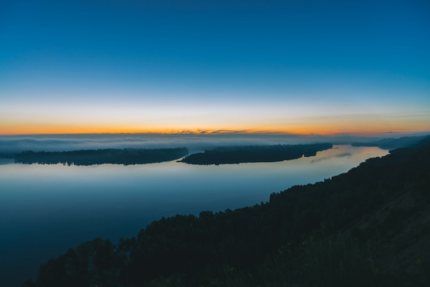 Vista da costa no rio largo. margem do rio com a floresta sob uma névoa espessa. amanhecer refletido na água. brilho amarelo no céu pitoresco antes do amanhecer.