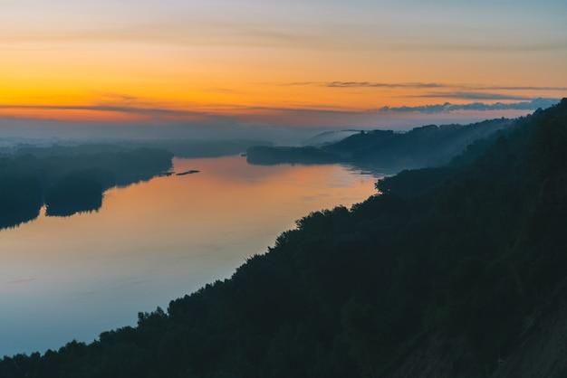 Vista da costa no rio. margem do rio com a floresta sob uma névoa espessa. amanhecer de ouro refletido na água. brilho amarelo no céu pitoresco antes do amanhecer. paisagem atmosférica da manhã colorida de natureza majestosa.