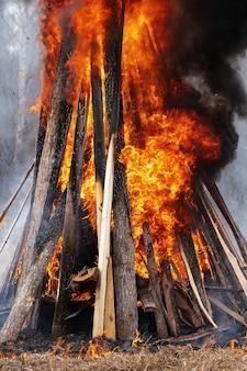 Vista da enorme fogueira de tábuas de madeira e pneus de automóveis, forte chama de fogo vermelho, ondulando a fumaça preta no céu.