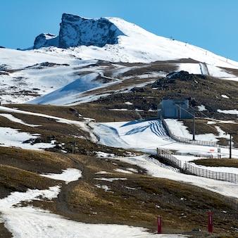 Vista da estação de esqui de sierra nevada, em granada, espanha, na baixa temporada de neve. usando canhões de neve artificiais
