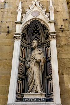 Vista da estátua de mármore de são pedro de donatello, no exterior da igreja orsanmichele em florença, itália