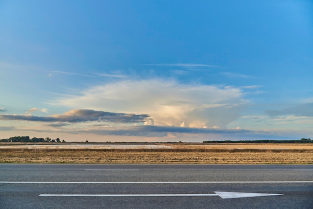 Vista da estrada com seta a frente e pôr do sol no campo.