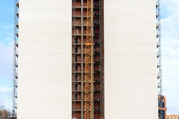 Vista da fachada posterior de um bloco de apartamentos em construção com um guindaste