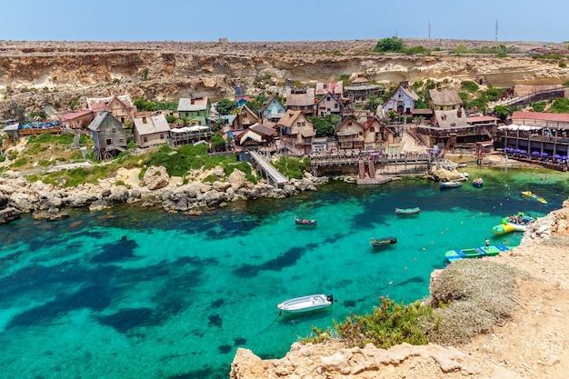 Vista da famosa vila de popeye com casas de madeira coloridas e o golfo de malta.