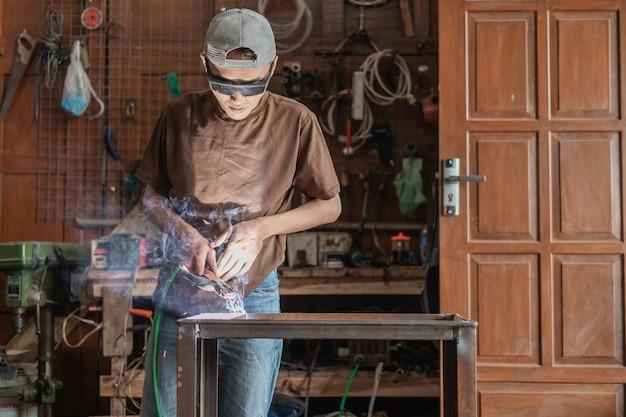 Vista da frente de um soldador usando óculos de soldagem pretos durante a soldagem