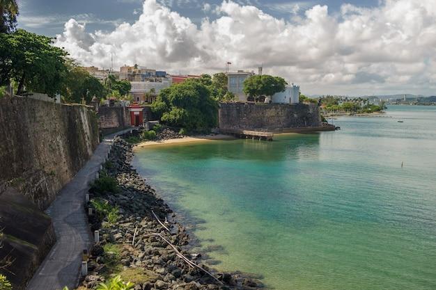 Vista da histórica cidade colorida de puerto rico à distância com parede de proteção.