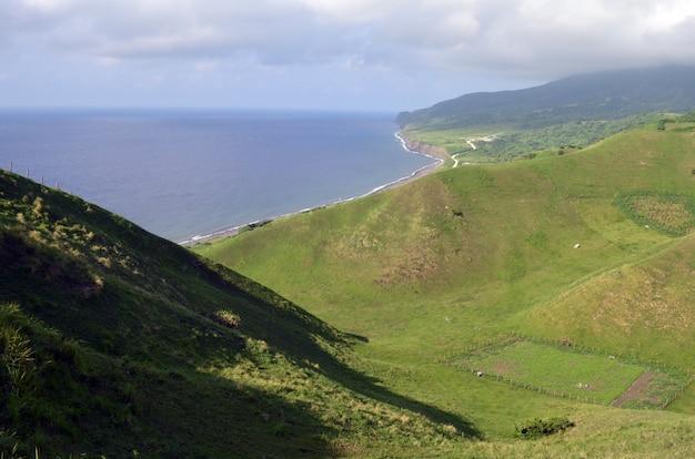 Vista da ilha coberta de vegetação ao redor de um mar de um ponto alto