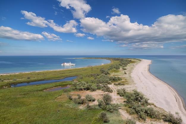 Vista da ilha, uma foice no mar, contra o fundo de um céu azul com nuvens