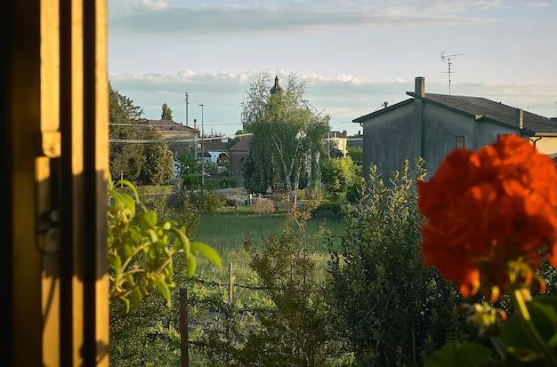 Vista da janela aberta de uma paisagem rural típica das pequenas aldeias do vale do pó, na itália, com flores e plantas em plena floração. villanova del ghebbo, itália, local da foto.