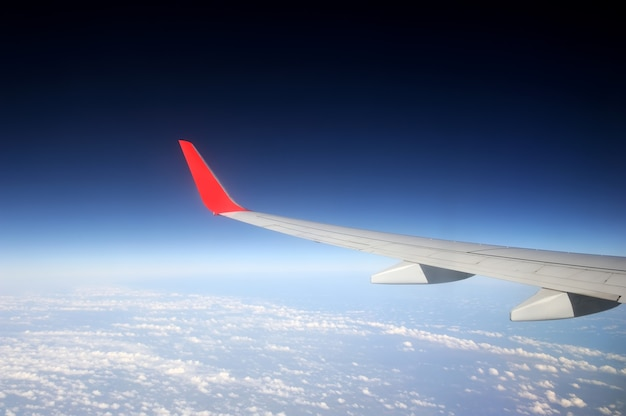 Vista da janela do avião com céu azul e nuvens brancas