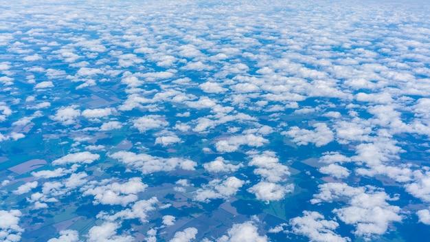 Vista da janela do avião vendo pequenos grupos de nuvens se espalhando e flutuando no céu azul como algodões acima da terra da rússia cobrindo com sombras de nuvens em algumas partes da paisagem