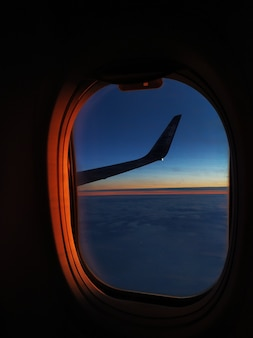 Vista da janela do avião voando sobre o mar ao pôr do sol.