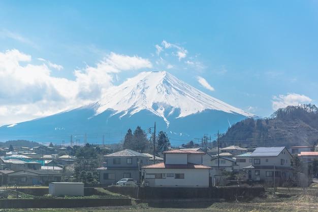 Vista da janela do trem com monte fuji no fundo do céu azul.
