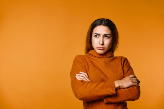 Vista da jovem mulher caucasiana pensativa vestida de pullove, seriamente focada