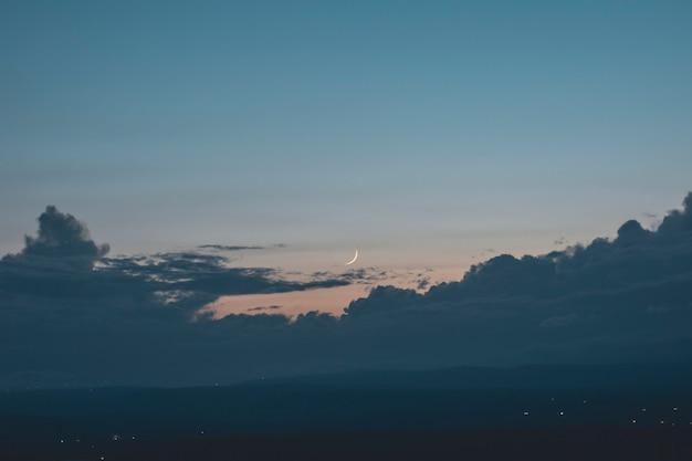 Vista da lua através das nuvens ao pôr do sol