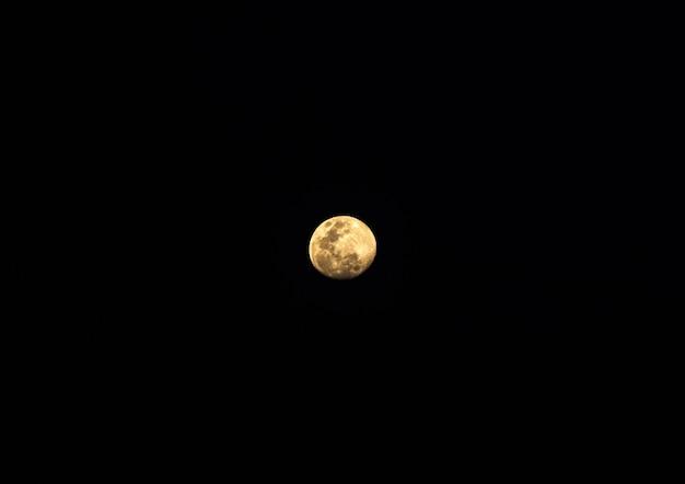 Vista da lua cheia está brilhando na noite escura, céu claro no verão, vista frontal com o espaço da cópia.