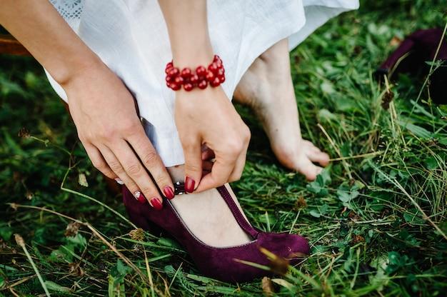 Vista da mão feminina calça sapatos de casamento. a noiva tirando os sapatos do estilo rústico. noiva estilo ucraniano com roupas bordadas.