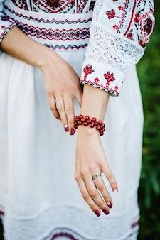 Vista da mão feminina com laca vermelha nas unhas e usa uma pulseira de pedras preciosas. noiva estilo ucraniano com roupas bordadas.