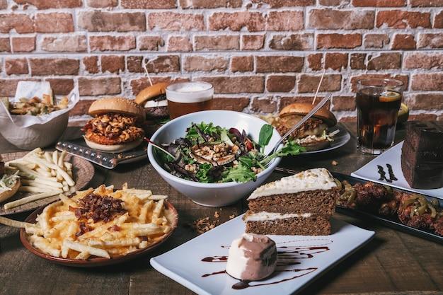Vista da mesa com hambúrgueres, batatas fritas e salada, bebidas e bolo e sobremesas na mesa de madeira.