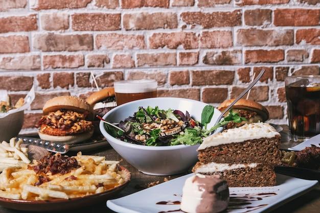 Vista da mesa com hambúrgueres, batatas fritas e salada, bebidas e bolo na mesa de madeira, imagem isolada.