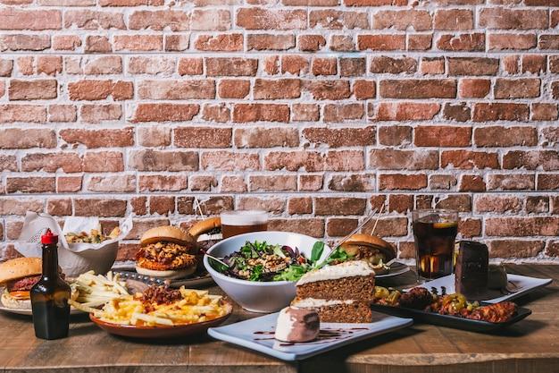 Vista da mesa com uma variedade de pratos, hambúrgueres, batatas fritas e salada, bebidas, asas de frango, molho, bolo e sobremesas na mesa de madeira. cardápio do restaurante.