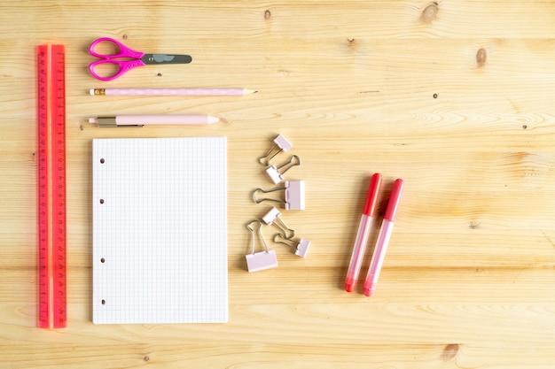 Vista da mesa de madeira com régua de plástico vermelha, tesoura rosa, caneta, lápis, grupo de clipes, caderno e dois marcadores de texto na parte superior