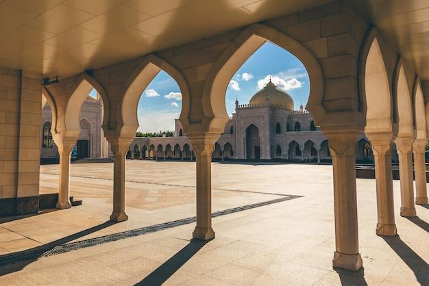 Vista da mesquita branca à luz do pôr do sol através dos arcos