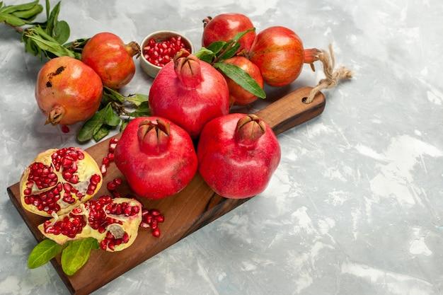 Vista da metade do topo das romãs vermelhas frescas frutas azedas e maduras na mesa branca clara