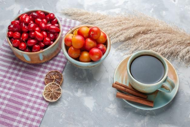 Vista da metade do topo dogwoods vermelhos frescos com chá na mesa branca frutas chá fresco maduro