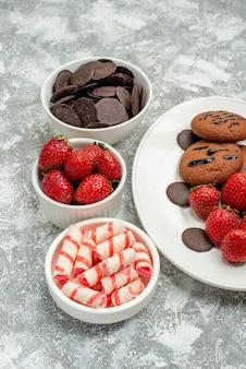 Vista da metade inferior, cookies de chocolate, morangos e chocolates redondos no prato oval branco e tigelas com doces e morangos chocolates no fundo branco-acinzentado