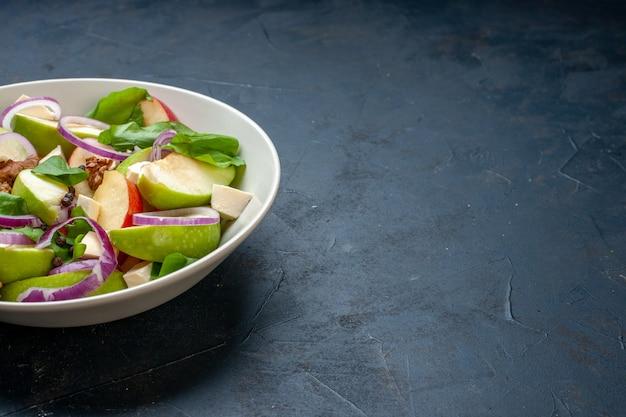 Vista da metade inferior da salada de maçã fresca em uma tigela no local de cópia da mesa azul escuro